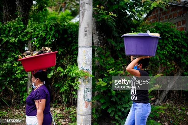 Women wearing protective masks carry vegetables to sell to their neighbors during government issued lockdown on May 18 2020 in Cuscatlan El Salvador...