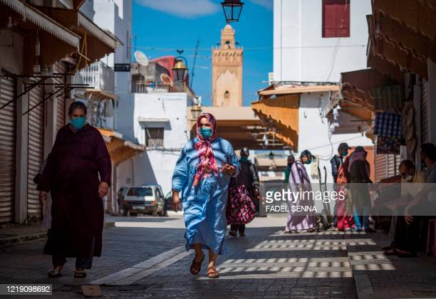Women, wearing protective masks due to the COVID-19 pandemic, pass through a street in the Moroccan capital Rabat on June 10 as the government...