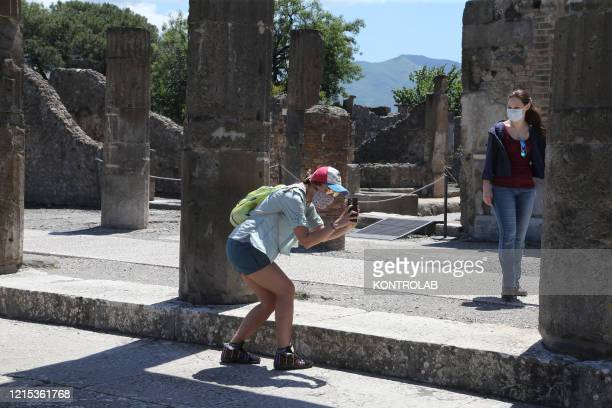 Women wearing protective masks visit and take pictures with a smartphone in the reopened archaeological site of Pompeii, the ancient Roman town...