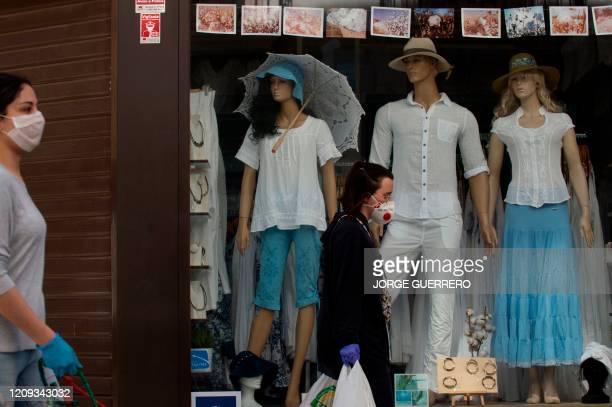 Women wearing protective masks walk by a closed store on April 7 in Ronda, as Holy Week processions were cancelled during a national lockdown to...
