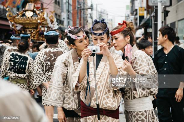 Women wearing quothappiquot coats look at the photo they took during Tokyo's one of the largest three day festival called quotSanja Matsuriquot on...