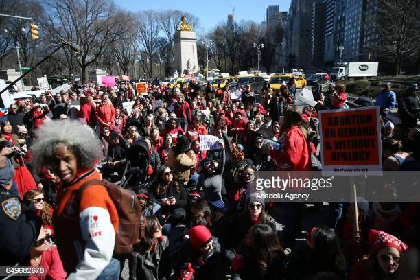 Women wearing red clothes take part in International Women's Day march in Manhattan borough of New York United States on March 8 2017