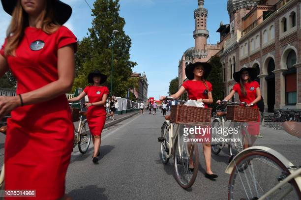 Women wearing red dresses walk with their bicycles during the 75th Venice Film Festival on August 29 2018 in Venice Italy