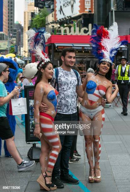 Women wearing red white and blue body paint and little else pose for tips with tourists in Times Square on June 10 2017 in New York New York With a...
