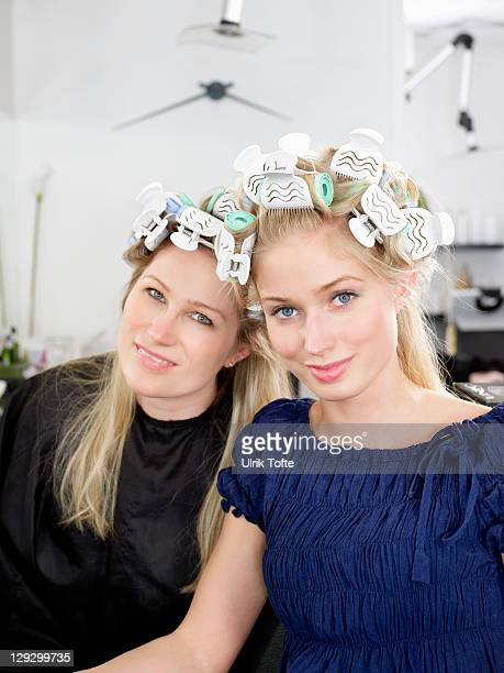 Women wearing rollers in salon