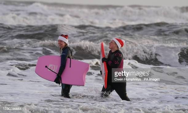 Women wearing santa hats bodyboarding on Christmas Day at Tynemouth Beach on the North East coast.
