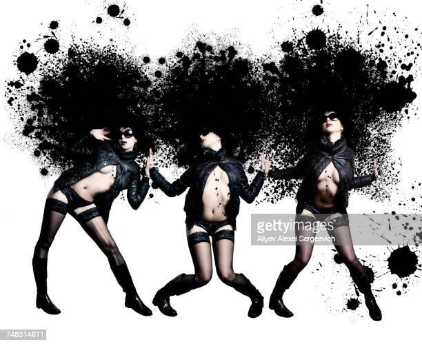 Women wearing stockings and jackets near black paint splatter