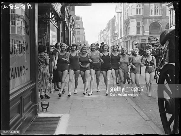 Women wearing swimsuits in a London street, 1932. A photograph of a line of women in swimsuits walking through London's West End, taken by Tomlin for...