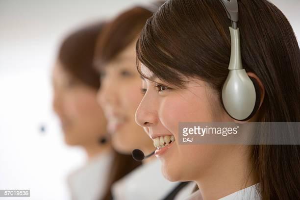 Women wearing telephone headset, smiling