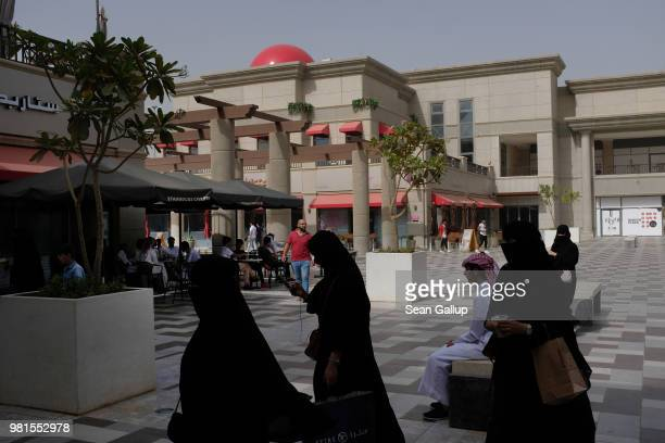 Women wearing the traditional Saudi niqab and black abaya walk across the central courtyard of Rubeen Plaza a shopping center popular with young...