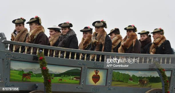 Women wearing their traditional costumes of the region sit on a horse-drawn carriage during the traditional Leonhardi pilgrimage drive in Bad Toelz,...