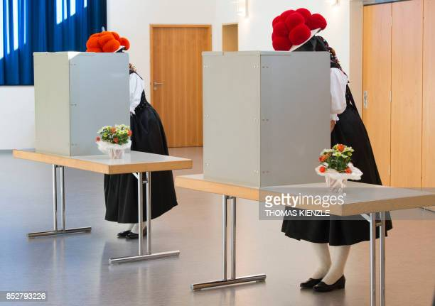 Women wearing traditional 'Bollenhut' pompon hats typical for the Black Forest region fill out their ballot papers at a polling station in Gutach...
