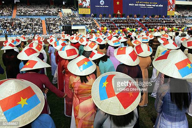 Women wearing traditional conical hats painted with national flags and flags of the former Southern Viet Cong government attend a ceremony 29 March...
