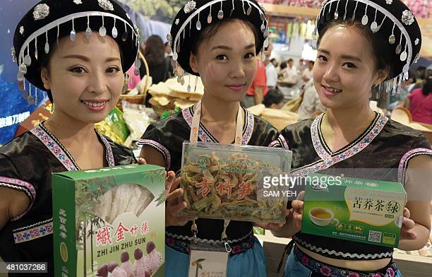 Women wearing traditional dress from the southwestern Chinese province of Guizhou display items from the region during the Taiwan Culinary Exhibition...