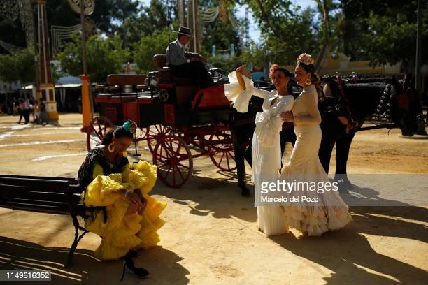 Women wearing traditional flamenco dresses take a selfie during the 'Feria del Caballo' on May 16, 2019 in Jerez de la Frontera, Spain. The Jerez...