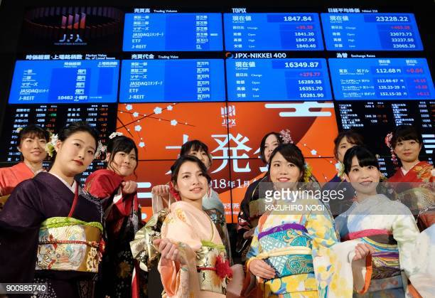 Women wearing traditional kimono outfits pose after the opening of the stock market for the year at the Tokyo Stock Exchange on January 4 2018 Tokyo...