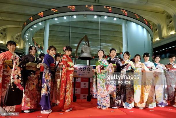 Women wearing traditional kimono outfits pose after the opening of the stock market for the year at the Tokyo Stock Exchange in Tokyo on January 4...