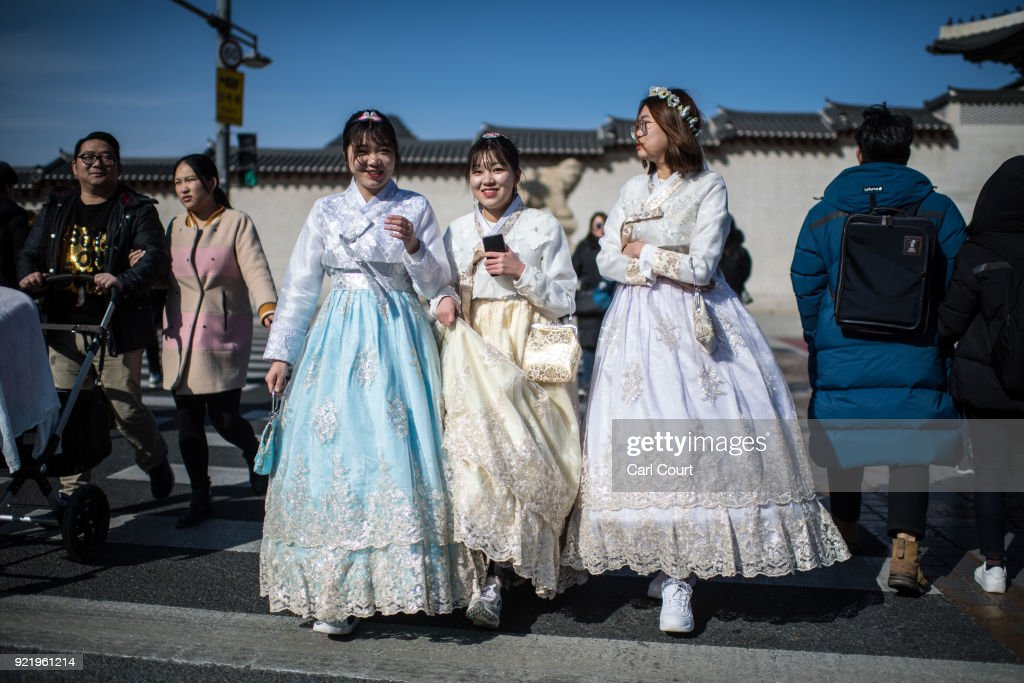 Women wearing traditional Korean Hanbok dresses cross a road near Gyeongbokgung Palace on February 21, 2018 in Seoul, South Korea. With tourists visiting from around the world, leaders from South Korea's capital as well as GyeongGi and Gangwon Provinces have agreed to work together to support the PyeongChang Olympic Games and to invigorate regional tourism.