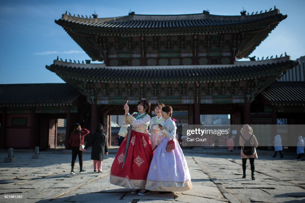 Women wearing traditional Korean Hanbok dresses take a selfie photograph as they visit Gyeongbokgung Palace on February 21, 2018 in Seoul, South Korea. With tourists visiting from around the world, leaders from South Korea's capital as well as GyeongGi and Gangwon Provinces have agreed to work together to support the PyeongChang Olympic Games and to invigorate regional tourism.