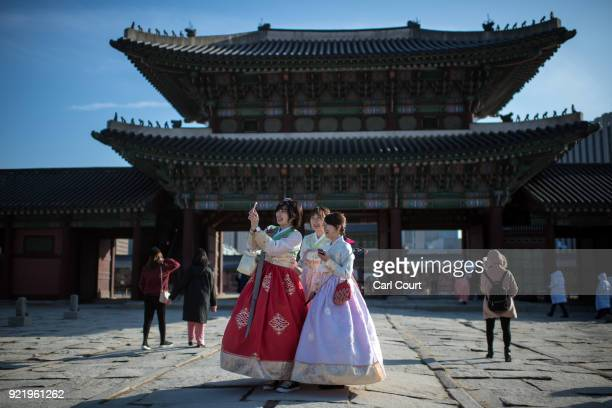 Women wearing traditional Korean Hanbok dresses take a selfie photograph as they visit Gyeongbokgung Palace on February 21 2018 in Seoul South Korea...