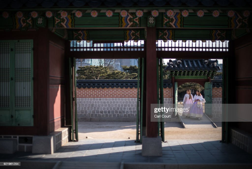 Women wearing traditional Korean Hanbok dresses walk through a doorway as they visit Gyeongbokgung Palace on February 21, 2018 in Seoul, South Korea. With tourists visiting from around the world, leaders from South Korea's capital as well as GyeongGi and Gangwon Provinces have agreed to work together to support the PyeongChang Olympic Games and to invigorate regional tourism.