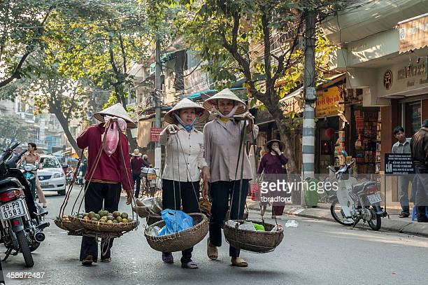 women wearing traditional non la hats in hanoi, vietnam - avenue stock pictures, royalty-free photos & images