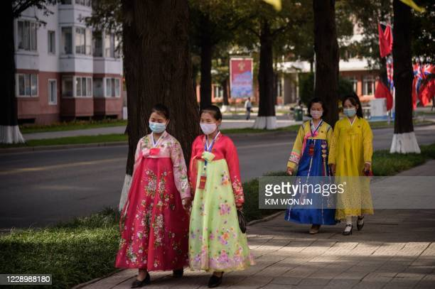 Women wearing traditional North Korean Chosunot dresses walk on a street as the country marks the 75th founding anniversary of the Workers' Party of...