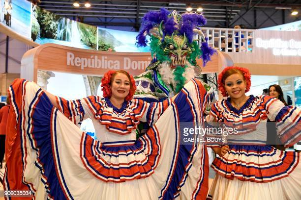 Women wearing traditional outfits pose at the Dominican Republic stand during the International Tourism Fair in Madrid on January 17 2018 / AFP PHOTO...