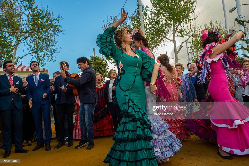 Women wearing traditional Sevillana dresses dance a Sevillana at the Feria de Abril (April's Fair) on April 12, 2016 in Seville, Spain. The Feria de Abril has a history that dates back to 1857 and takes place a fortnight after Easter each year. The origin of the fair was a cattle market but the event quickly turned its goal from commerce to having fun. More than 1 million local and international participants are expected to attend the Feria de Abril.