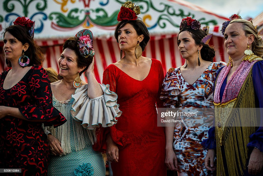 Women wearing traditional Sevillana dresses enjoy the atmosphere at the Feria de Abril (April's Fair) on April 12, 2016 in Seville, Spain. The Feria de Abril has a history that dates back to 1857 and takes place a fortnight after Easter each year. The origin of the fair was a cattle market but the event quickly turned its goal from commerce to having fun. More than 1 million local and international participants are expected to attend the Feria de Abril.