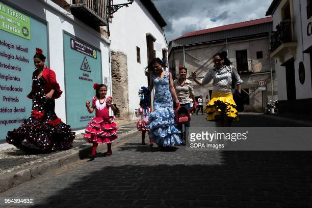 Women wearing typical flamenco dresses walking along the streets of Albaicin neighbourhood El día de la Cruz or Día de las Cruces is one of the most...