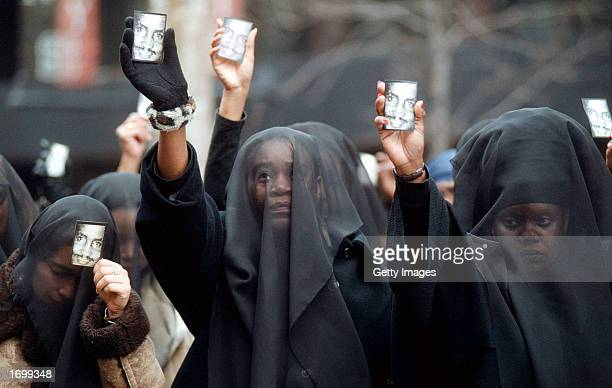 Women wearing veils of mourning hold cards with the image of Amadou Diallo before the start of a prayer vigil outside the United Nations February 27...