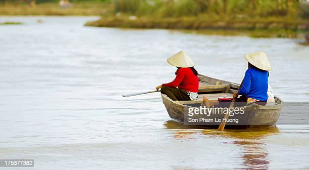 Women wearing Vietnamese traditional conical hat row at little wooden boat on Thu Bon river, Hoi An, Vietnam on Nov 10, 2011