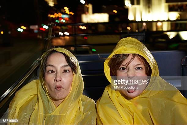 Women wearing waterproofs on open top bus