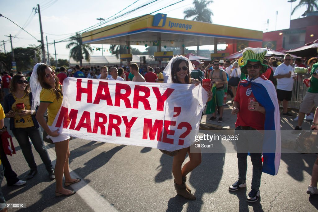 Women wearing wedding veils hold a banner proposing marriage to Britain's Prince Harry outside the Mineirao Stadium after watching England play Costa Rica on June 24, 2014 in Belo Horizonte, Brazil. England drew 0-0 with Costa Rica in their final game of Group D in the 2014 FIFA World Cup, the result sees England finish at the bottom of the group table with Costa Rica at the top.