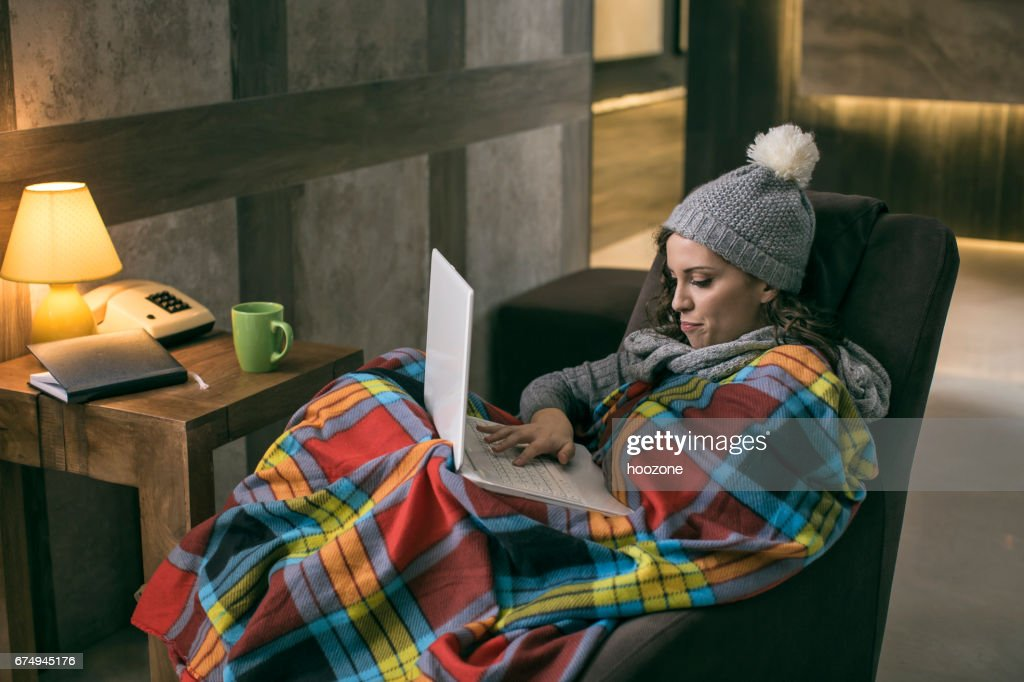 Women wearing winter cap working on laptop wrapped in a blanket at home with no heating : Stock Photo