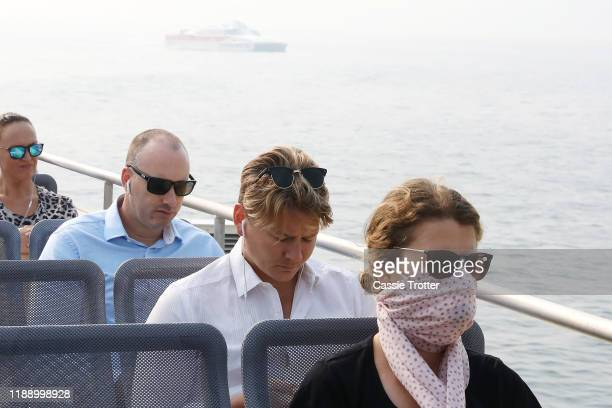 A women wears a face mask while traveling on a ferry as smoke haze shrouds Sydney Harbour on November 21 2019 in Sydney Australia Most of NSW remains...