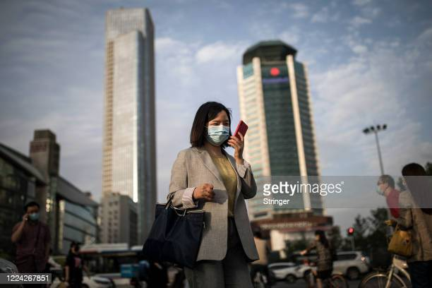Women wears a mask while uses iPhone pass the crossroads on May 11, 2020 in Wuhan, China. The government has begun lifting outbound travel...