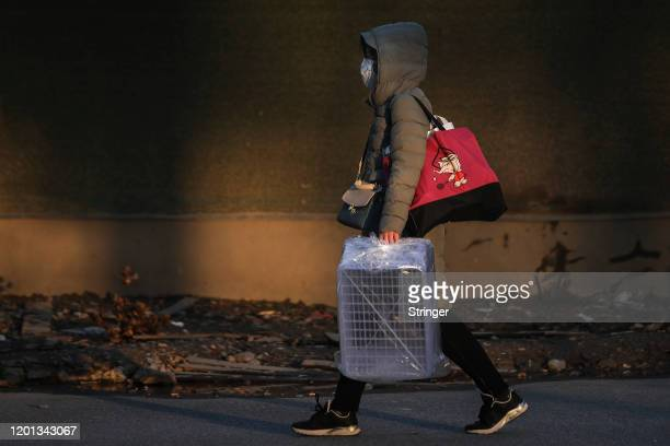 Women wears a protective mask as she carry a empty basket walk in the street at Optical Valley on February 16, 2020 in Wuhan, Hubei province, China....