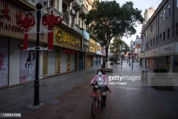 Women wears a protective mask as she cycling bike at the empty business street on February 13, 2020 in Wuhan, Hubei province, China. Flights, trains...