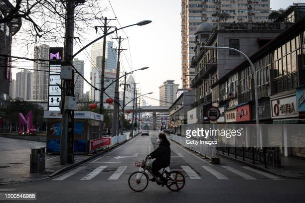 Women wears a protective mask as she ride a bicycle in the empty business street on February 13, 2020 in Wuhan, Hubei province, China. Flights,...