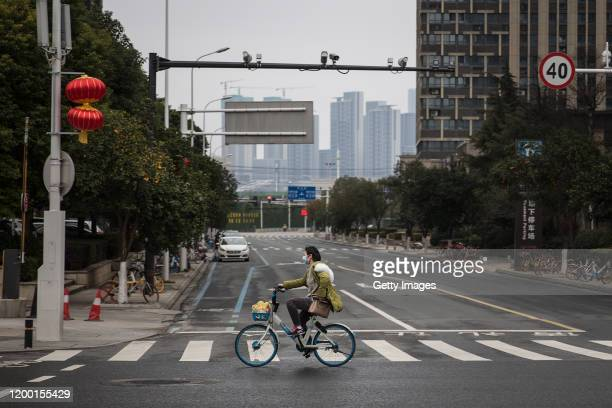 A women wears a protective mask as she rides a bicycle on February 112020 in Wuhan Hubei provinceChina Flights trains and public transport including...
