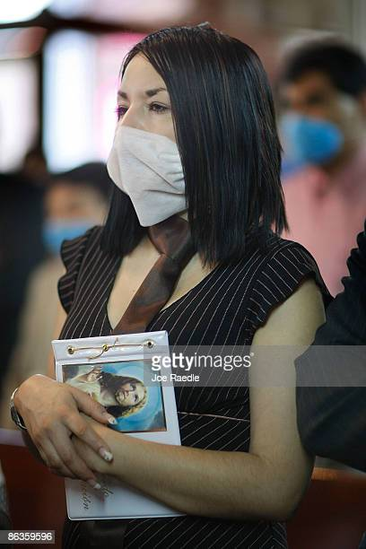 A women wears a surgical mask to help prevent catching the swine flu during a church service on May 3 2009 in Mexico City Mexico The Mexican...