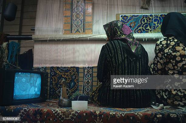 Women weaving a carpet in a house watch television while working in Isfahan, 25th August 1995.