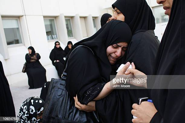 Women weep outside a hospital morgue after at least three people died and hundreds were left injured when police stormed an antigovernment protester...