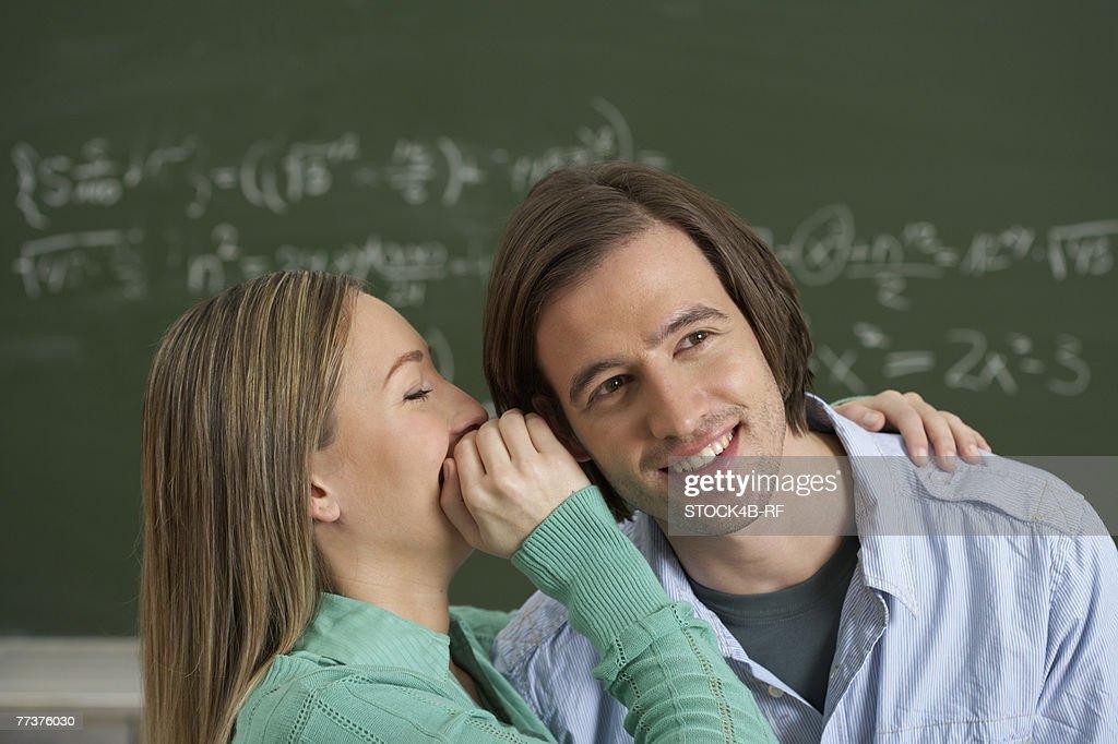 A women whispering in mans ear  : Photo