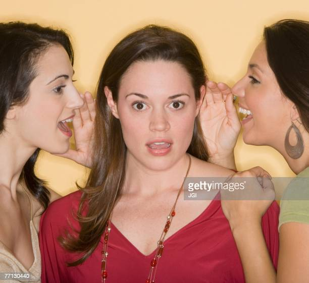Women whispering secrets to friend