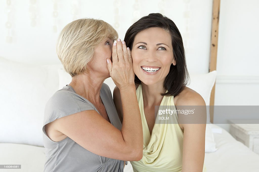 Women whispering to each other : Stock Photo