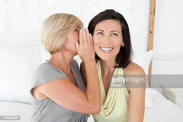 Women whispering to each other