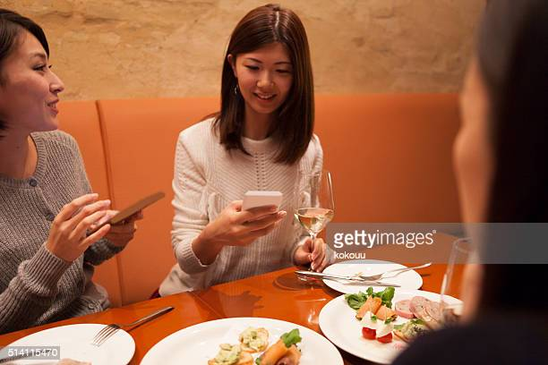 女性がスマートフォンをご覧になるには、笑いのレストランで